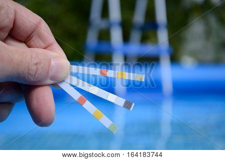 Hand with measuring strips to control water quality in swimming pools