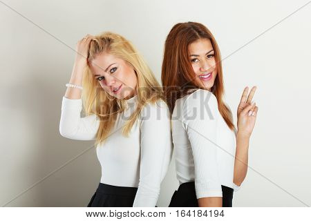 People colleagues concept. Blonde and dark friends together. Bright girl posing with mulatto lady.