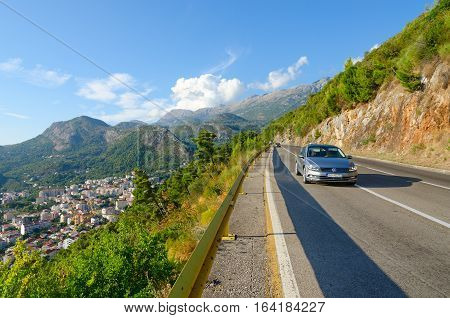 BUDVA MONTENEGRO - SEPTEMBER 23 2015: Young couple is traveling in passenger car on narrow mountain road over coast of Budva Montenegro