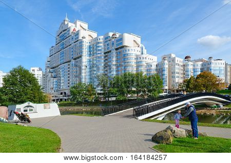 MINSK BELARUS - OCTOBER 1 2016: Unidentified people are walking on Island of Tears near Humpback bridge over Svisloch and residential complex
