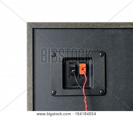 Red and black twisted wire connected to cable connection socket on rear side speaker system box front view vertical photo isolated closeup