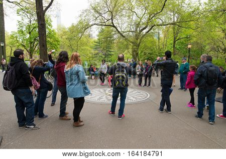 NEW YORK - APRIL 28 2016: Tourists at the Imagine mosaic commemorating John Lennon at Strawberry Fields in Central Park