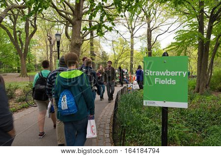 NEW YORK - APRIL 28 2016: Tourists visit strawberry fields in central park. It is a 2.5-acre (1.0 ha) landscaped section in Central Park that is dedicated to the memory of former Beatle John Lennon.