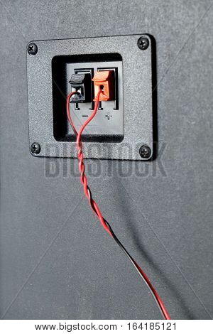 Red and black twisted wire connected to cable connection socket on rear side speaker system box side view vertical photo closeup
