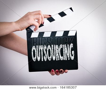 Outsourcing. Female hands holding movie clapper. Gray background