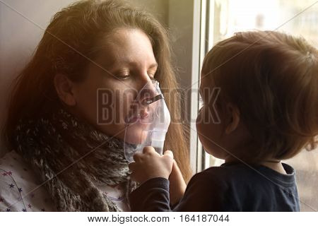 Sick girl with a sore throat makes inhalation with a mask on his face sitting in the window. Son helps his mother to do the inhalation nebulizer