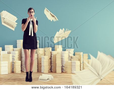 young woman standing infront of stack books.