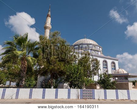 Mosque on sunny summer day with blue sky and clouds