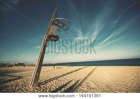 Wide angle shot of wooden lookout lifeguard tower at Barceloneta beach on sunny summer day with clear teal sky and sea in the background flying seagull on the left long shadows on sand Barcelona