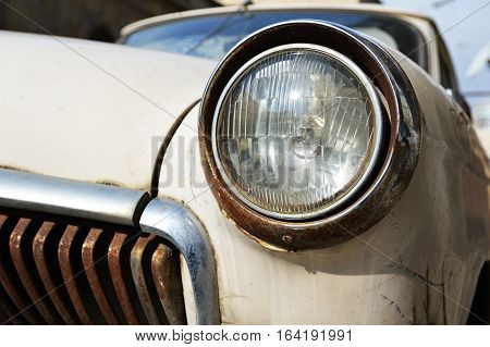 Old rusted white car headlight close up foreground