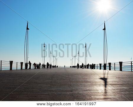 Silhouettes of people on the seaside bridge