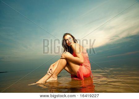 Beautiful girl sitting on water