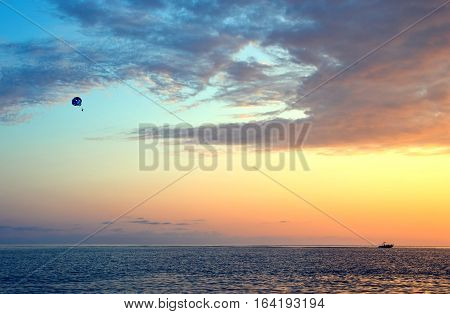 Boat with parachute on the background of beautiful cloudy sunset