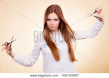 Craziness of professional hairdresser. Hair hygiene. Girl with scissors making crazy funny face preparing herself to cutting styling new image hairdo coiffure.