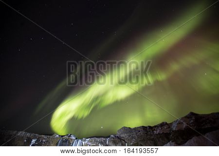 Northern lights dancing over in the Icelandic winter sky