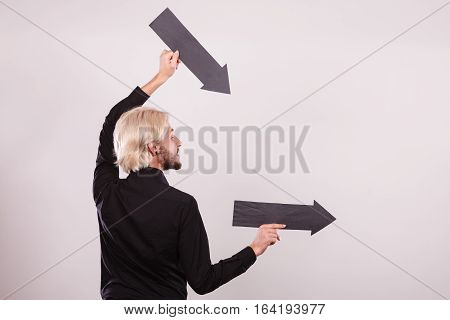 Planning directions choices concept. Man holding two black arrows pointing right. Indoor shot on light background