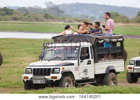 MINNERIYA, SRI LANKA. July 21, 2016: Minneriya National Park. A jeep carrying many tourists visiting the famous national park of Sri Lanka. A row of cars goes into the park in search of wild animals.