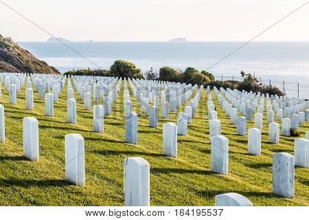 Tombstones at Fort Rosecrans National Cemetery in San Diego, California with Los Coronados islands in the background.