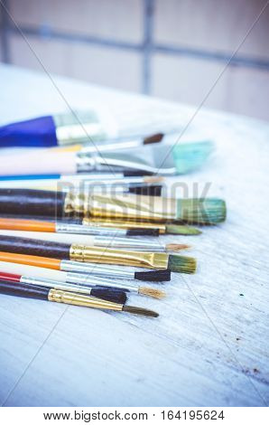 Artist paint brushes on white wooden background. Brush paint artistic. Tools for creative work. Watercolor paintbrush. Back to school. Paintings Art Concept. Selective focus. Copy space.