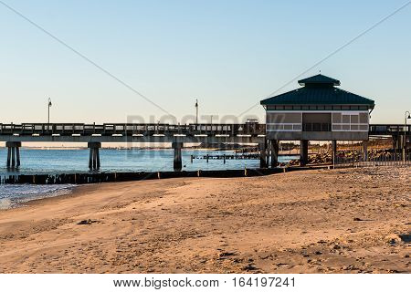 Morning light on fishing pier with sandy beach at Buckroe Beach in Hampton, Virginia.