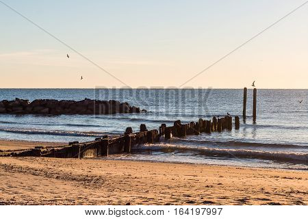 Dock pilings and rock jetty at sunrise at Buckroe Beach in Hampton, Virginia.