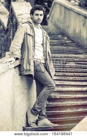 Handsome man on outdoor old staircase. A handsome young Italian man is leaning on a wall of a staircase in the historic center of Rome, Italy. He dresses winter clothes, coat and pants. Black and white with soft warm tones hue.