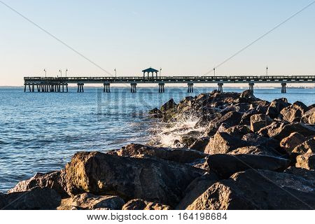 Waves crash on jetty at Buckroe Beach in Hampton, Virginia with fishing pier in background.