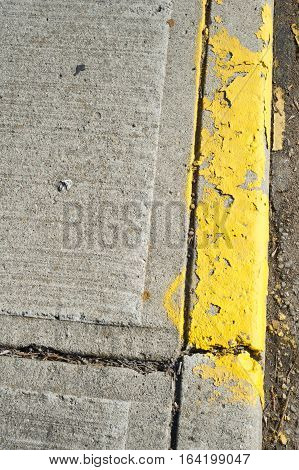 Close up of sidewalk where the side has been painted yellow for a indication of no parking. The cement is old and the paint has been worn away.