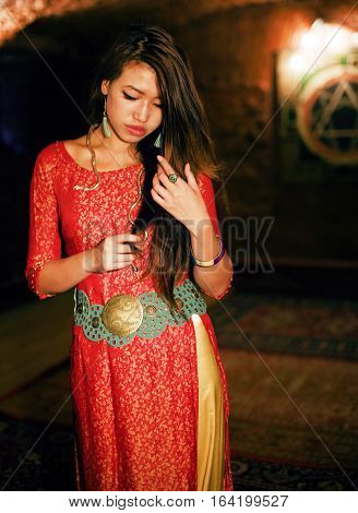 young pretty asian girl in bright colored interior on carpet view, oriental concept