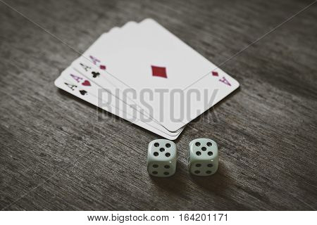 four aces playing cards and two dice number double five on a wooden background. risk, luck, abstraction. Space for your text or object