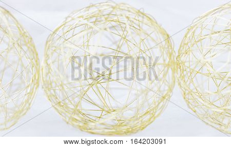 horizontal image a round ball of gold wire with two half wire balls on either side on white background.