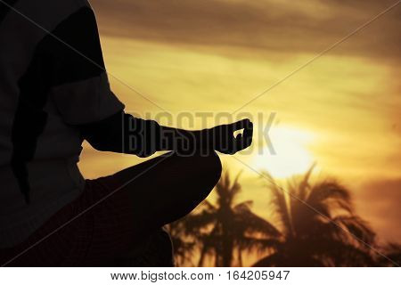 silhouette hand of a woman meditating in a yoga pose on the beach at sunset