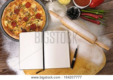 Making a pepperoni Pizza with blank cookbook for recipe and various ingredients.