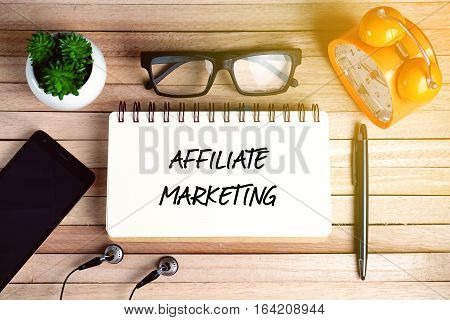 Top view of earphone, smartphone, plant, eye glasses, alarm clock, pen and open notebook written with AFFILIATE MARKETING on wooden background. Business Concept.