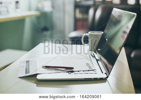 Office table with Laptop tablet and resume information. Job search concept.