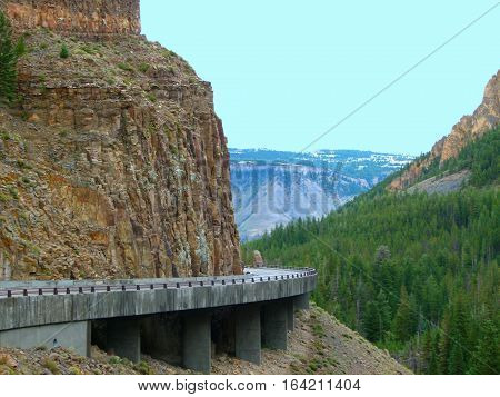 A winding road around a mountain, with mountains to the side and mountains in the background.  Inside Yellowstone National Park.