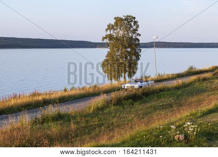 BALTIC SEA, SWEDEN ON JULY 26. View of a white car, passenger and an inlet on July 26, 2013 by the Baltic Sea, Sweden. Slope, grass and sunshine. Unidentified persons. Editorial use.