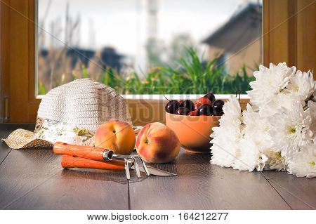 Country still life. The harvest from the garden - cherries peaches. Chrysanthemum flowers garden tools and summer hat on the window sill