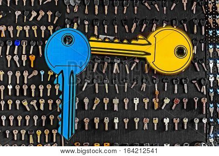 Blue and yellow big keys on a special wall with keys in a workshop