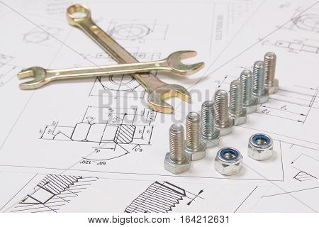 Technical drawings of bolts and nuts. Engineering, technology and metalworking. Metal bolts, nuts and wrench on printed drawings background.