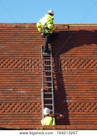 Two men working on a roof off a ladder