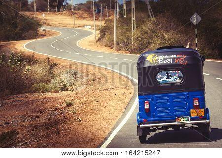 TISSAMAHARAMA, SRI LANKA. July 29, 2016: Tuk-tuk auto rickshaw on the road in Tissamaharama in Sri Lanka. Bajay or Bajaj is a motorized development of the traditional pulled rickshaw or cycle rickshaw.