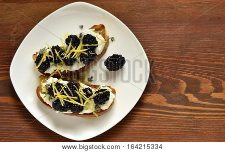Crostini with goat cheese blackberries lemon zest and honey, top view, copy space