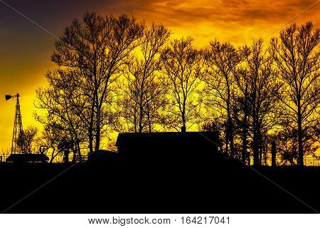 Silhouette of farmhouse, trees and windmill with a beautiful bright orange sunset background.