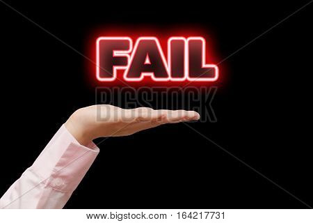 Business woman hand cupped holding the word FAIL with red neon light