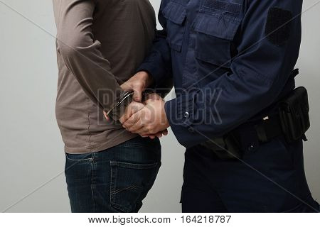 Closeup of a policeman handcuffing an illigal man.