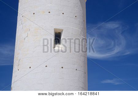 Window of old Paphos lighthouse white wall against blue sky, Cyprus island, Mediterranean coast,  Europe