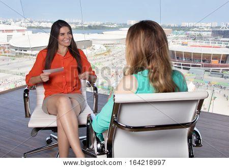 Latin female presenter interviewing a blonde caucasian celebrity at tv studio
