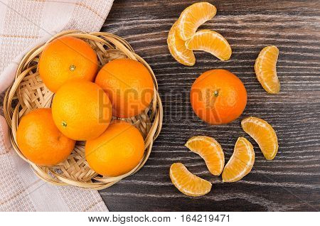 Wicker Basket With Tangerines And Slices Of Tangerines On Table