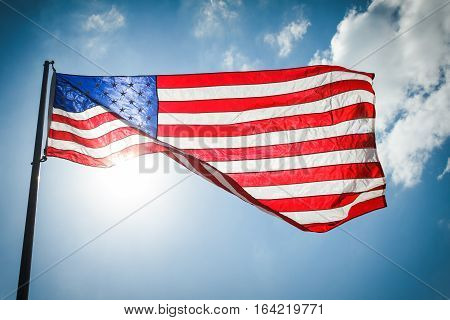 United States of America Flag with clouds and the sun shining through it